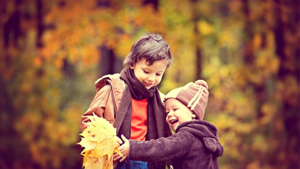 To barn i skog med høstfarger